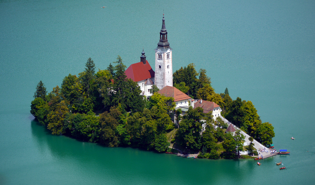 Zoom shot of the Church of the Assumption on a little island in the middle of lake bled